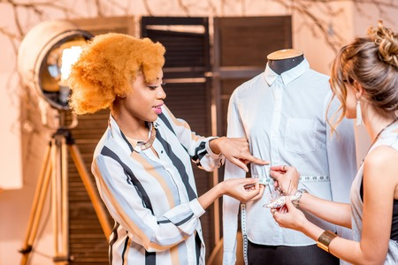 Two young multi-ethnic fashion designers working with mannequin at the studio Stock Photo