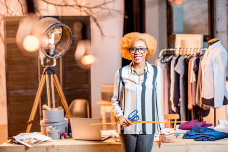 Portrait of a young african fashion designer standing with ruller at the office with different tailoring tools and clothes