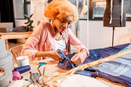 다른 재봉 도구와 옷을 입고 스튜디오에서 파란 직물로 작업하는 젊은 여성 재단사