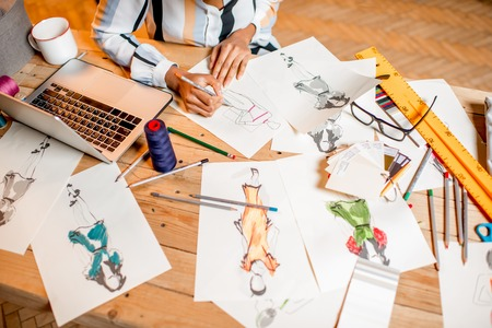 Fasion designer sketching clothes drawings at the table with tailoring tools and laptop