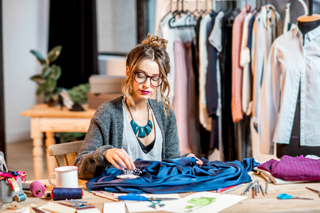Young female fashion designer working with blue fabric sitting at the beautiful office with different tailoring tools on the table Archivio Fotografico