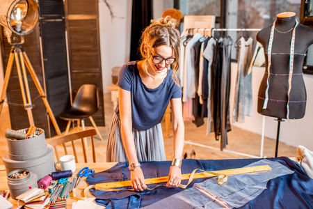 Young woman tailor working with ruller and blue fabric at the studio with different tailoring tools and clothes