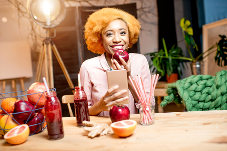 Portrait of a young african woman with fresh red fruits and smoothies sitting indoors at the cozy home interior