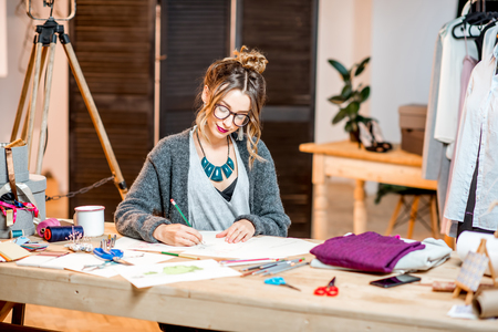 Young female fashion designer sketching drawings of the clothes sitting at the beautiful office with different tailoring tools