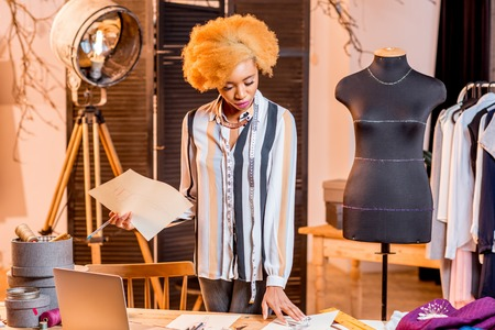 Young african fashion designer working with clothes drawings and laptop sitting at the studio interior with different tailoring tools