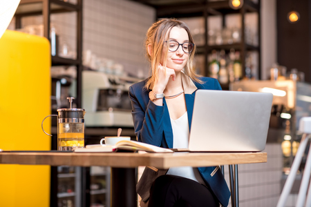 Young businesswoman strictly dressed in the suit working with laptop at the modern cafe interior