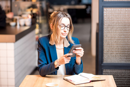 Young businesswoman strictly dressed in suit working with phone and notebook at the modern cafe interior
