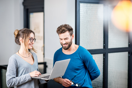 Couple of coworkers dressed casually standing with laptop near the wall at the modern cafe interior Stock Photo