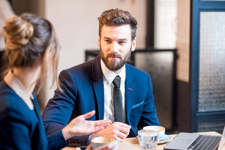 Conversation between business couple dressed in suits sitting with coffee at the cafe or restaurant Imagens