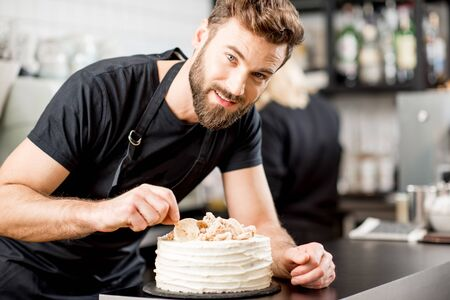 Handsome confectioner in black t-shirt decorating a pie at the bar of the modern cafe interior