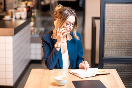 Young businesswoman strictly dressed in suit talking with phone working at the modern cafe interior