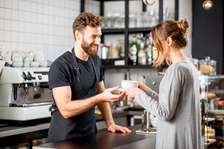 Handsome barista giving a coffee to the female client at the bar of the modern cafe