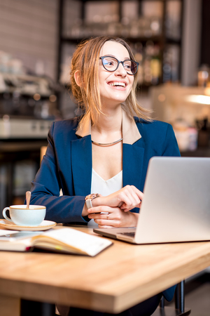 Portrait of a young businesswoman strictly dressed in the suit working with laptop at the modern cafe interior Stock Photo