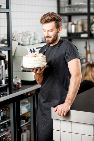 Portrait of a handsome bearded confectioner in black t-shirt and apron holding a pie at the cafe Zdjęcie Seryjne