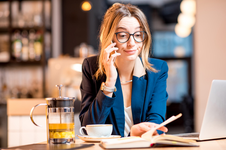 Disappointed businesswoman strictly dressed in the suit talking phone while working with laptop at the modern cafe interior Stock Photo