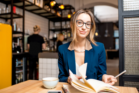Young businesswoman strictly dressed in suit working with notebook at the modern cafe interior Stock Photo