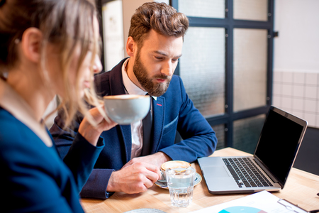 Caucasian business couple dressed strictly in the suits working together with laptop and paper charts sitting at the cafe during the coffee break