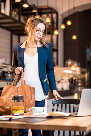 Young businesswoman strictly dressed in the suit coming with bag at the cafe table having a coffee break