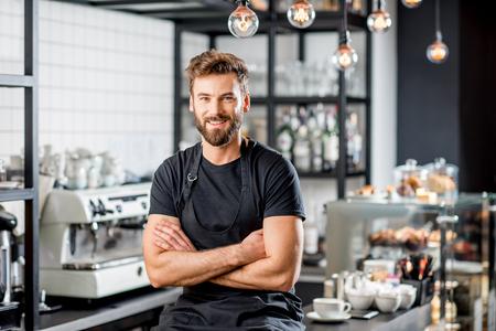 Portret van een knappe barista in zwart t-shirt en schort zitten aan de bar van het moderne café