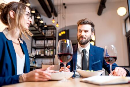 Caucasian business couple dressed strictly in the suits having discussion sitting together at the restaurant during the dinner Stock Photo
