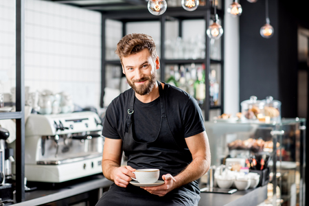 Portrait of a handsome barista sitting with coffee at the bar of the modern cafe interior 免版税图像 - 91959932