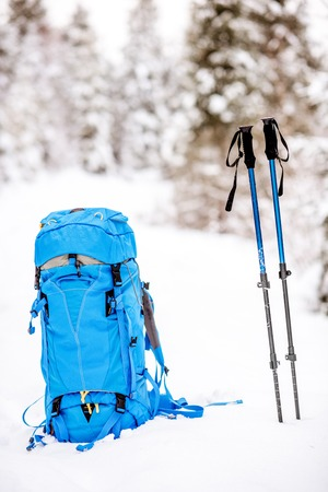 Blue backpack and tracking sticks at the snowy fir forest. Winter hiking concept