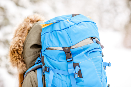 Close-up back view on the woman with blue backpack on the snowy forest background Stock fotó