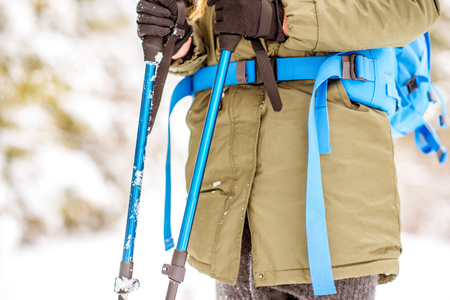 Close-up view on the female hands holding tracking sticks standing with backpack in the the snowy forest