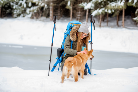 Woman having a break during the winter hiking stroking her dog at the snowy mountains near the lake and forest