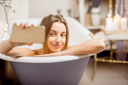 Young and beautiful woman making selfie photo with phone lying in the retro bath indoors