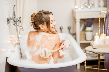 Young woman washing with brush in the beautiful vintage bath full of foam in the bathroom decorated with candles Archivio Fotografico