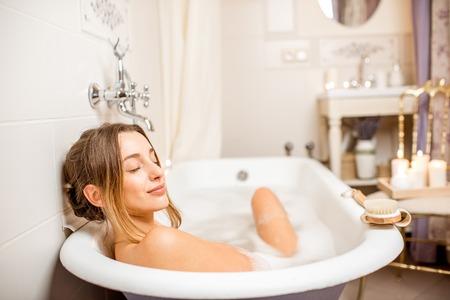 Het jonge vrouw ontspannen in het mooie uitstekende badhoogtepunt van schuim in de retro badkamers die met kaarsen wordt verfraaid Stockfoto