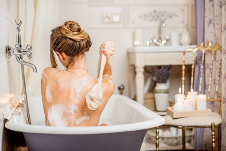 Young woman washing with brush in the beautiful vintage bath full of foam in the bathroom decorated with candles Stock Photo