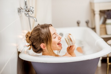 Junge Frau, die mit der Bürste voll sich entspannt im schönen Weinlesebad des Schaums im Badezimmer singt