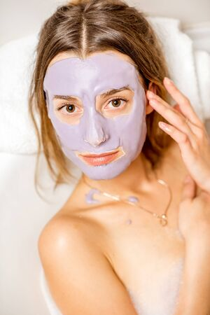 Close-up portrait of beautiful woman in the facial alginate mask lying on the towel Stock Photo