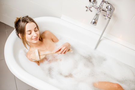 Top view on the young woman lying with brush in the bath full of foam Imagens