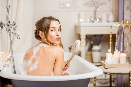 Young playful woman washing with brush in the beautiful vintage bath full of foam in the bathroom decorated with candles