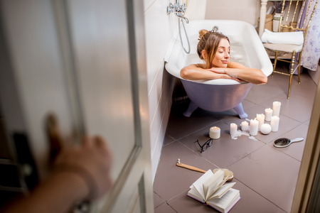 View through the bathroom door on the beautiful woman relaxing in the retro bathtub Stock Photo