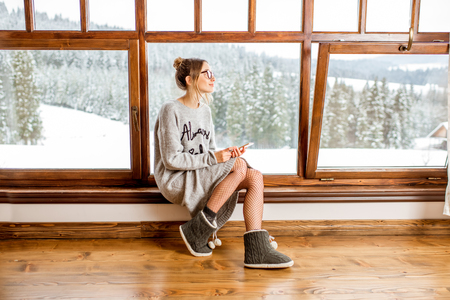 Junge Frau in der Strickjacke, die nahe dem großen Fenster am gemütlichen hölzernen Gebirgshaus mit schöner Landschaftsansicht während der Winterzeit sitzt Standard-Bild