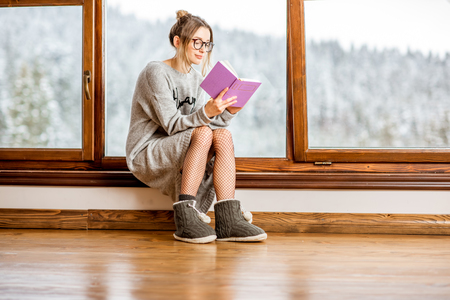 Young woman in sweater reading book near the window at the cozy wooden mountain house with beautiful landscape view during the winter time