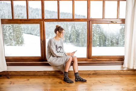冬の間に美しい風景の景色を持つ居心地の良い木造山の家の大きな窓の近くに座ってセーターの若い女性