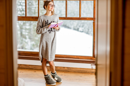 Young woman in sweater standing near the big window at the cozy wooden mountain house with beautiful landscape view during the winter time
