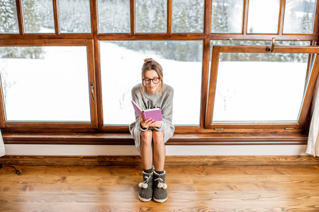 Young woman in sweater sitting near the big window at the cozy wooden mountain house with beautiful landscape view during the winter time