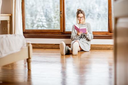 冬の間に美しい風景の景色を持つ居心地の良い木造山の家の窓の近くにセーター読書本の若い女性
