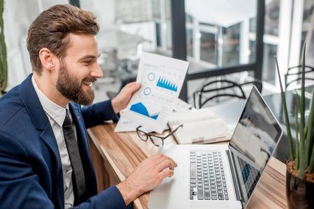 Portret van een knappe analytische manager die met document grafieken en laptop op het kantoor werkt Stockfoto
