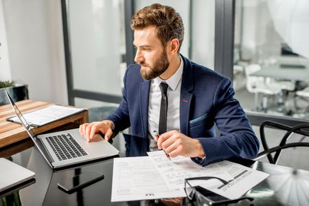 Handsome gestionnaire d & # 39 ; assurance habillée dans le costume travailler avec des documents et ordinateur portable à l & # 39 ; intérieur de bureau moderne Banque d'images - 92013310