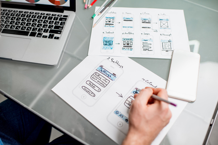 UX designer working on the mobile application experience sketching drawings at the office. Image focused no the drawsings cropped with no face 写真素材