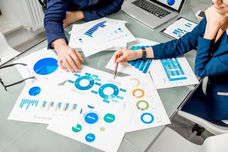 Marketeer of analityc manager team dat werkt aan papieren kaarten aan de tafel. Afbeelding gericht op de documenten
