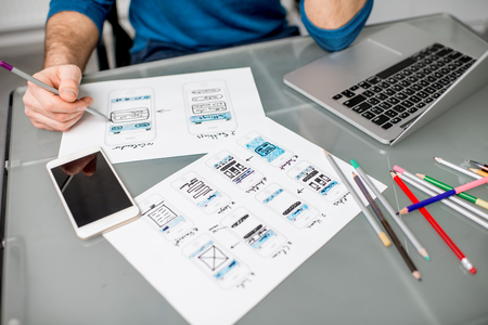 UX designer working on the mobile application experience sketching drawings at the office. Image focused no the drawsings cropped with no face Banque d'images