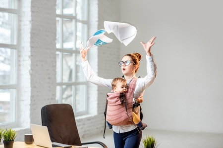 Multitasking and exhausted businesswoman throwing up a documents standing with her baby son during the work at the office Stockfoto